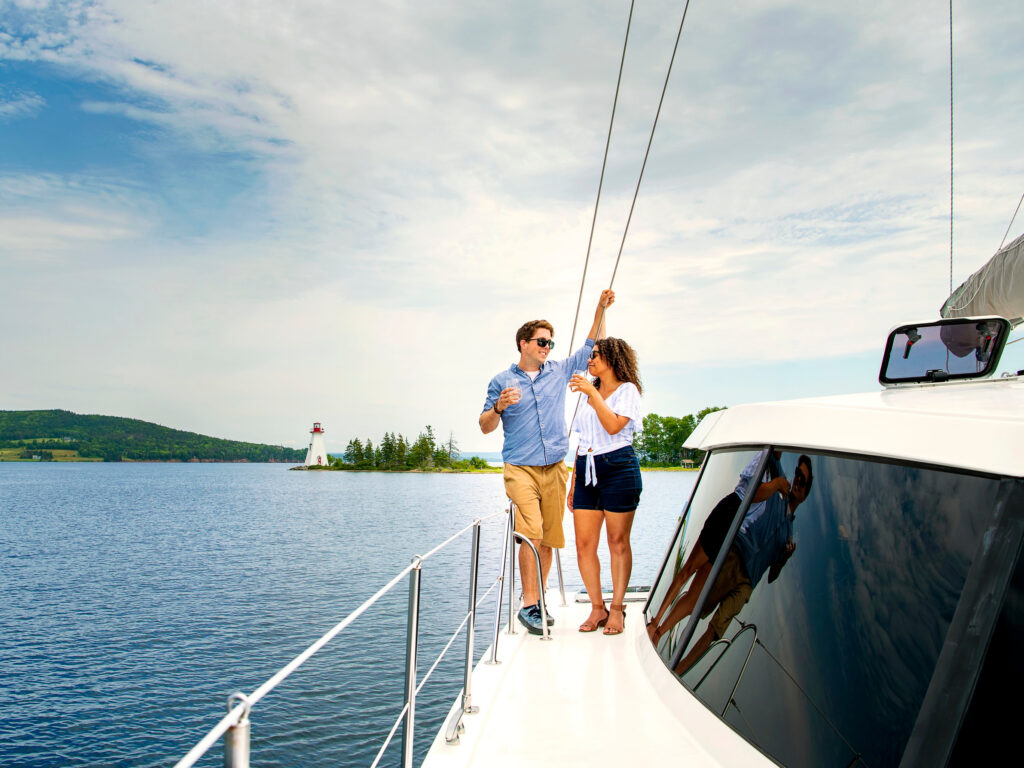 Couple enjoys a drink on the deck of the Cape Bretoner 1 catamaran with Baddeck Bay Lighthouse in the background